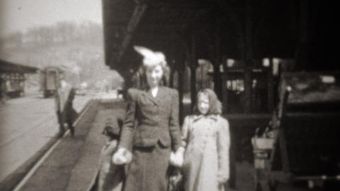 1941: Mother arrives at railroad train station holding daughters hands Footage