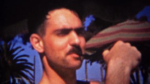 1944: Hispanic mustache man smoking pipe palm tree umbrella background Footage