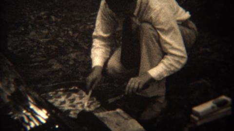 1937: Gourmet campfire cooking grilling pastries frying food Footage
