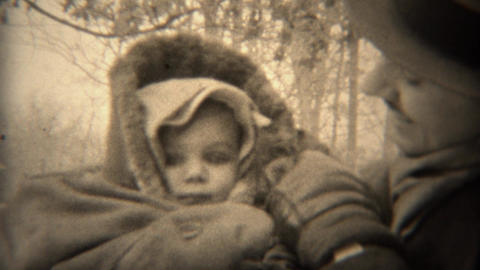 1937: Proud dad bundled up baby keeping warm in cold winter weather Footage