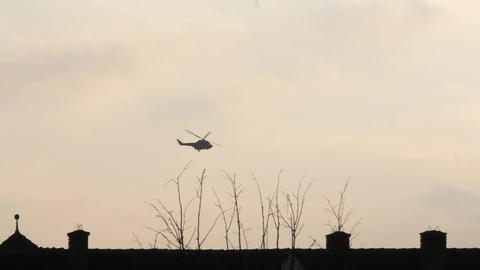 Helicopter flying at low height over the roofs of houses and trees in a small to Footage