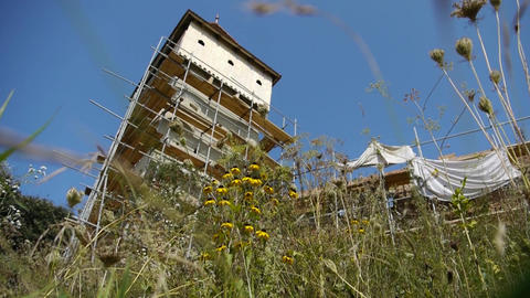 Image with the tower covered in scaffolding of an old fortress, surrounded by gr Footage