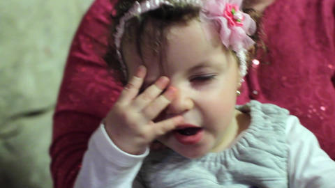 Year old girl who is held in the arms of her mother and plays with her hands 57d Footage