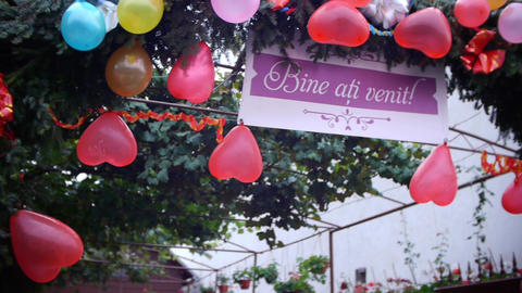 Multicolored balloons hung at the gate of the bride awaiting partygoers and groo Footage