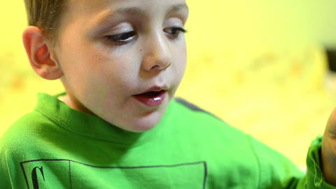 Boy dressed in a green shirt eat a candy lolly orange and is very happy 10 Footage