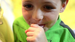 Boy dressed in a green shirt eat a candy lolly orange and is very happy 12 Footage