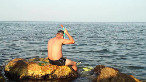 Man who is preparing to enter the sea He puts his paws fish to swim faster 33 Footage