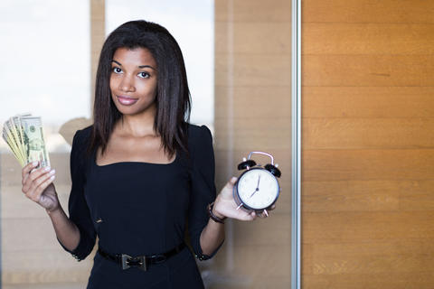 Pretty, young business lady in black strong suite hold a bundle of money and Photo