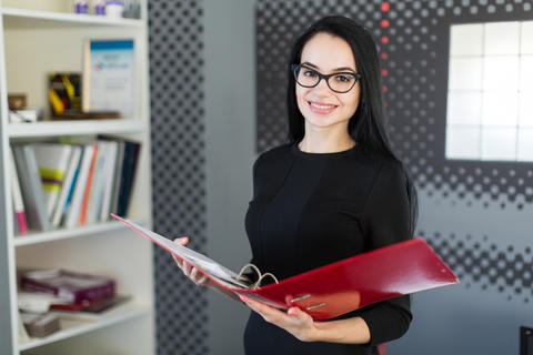 Beautiful young businesswoman in black dress and glasses hold paper folder Photo