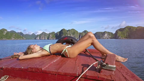 Pretty Blond Girl Takes Sunbathe on Boat against Quite Bay Live Action