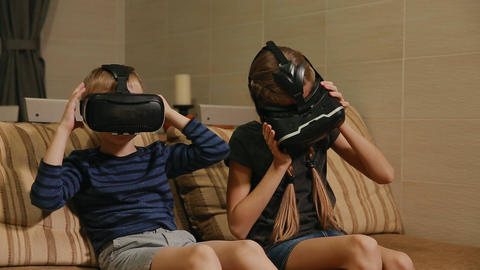 Brother with sister at home sitting on the couch playing the game using virtual Footage