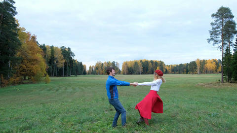 Outdoor portrait of happy couple holding hands and spinning around in a autumn Footage