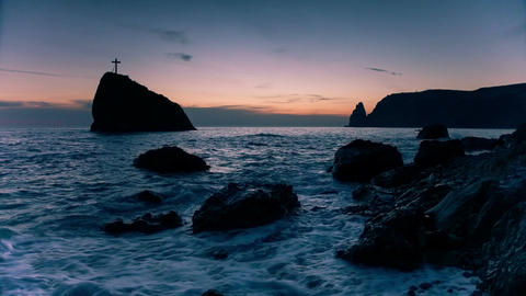 Cross on a rock in the sea, on the coast in the evening Image