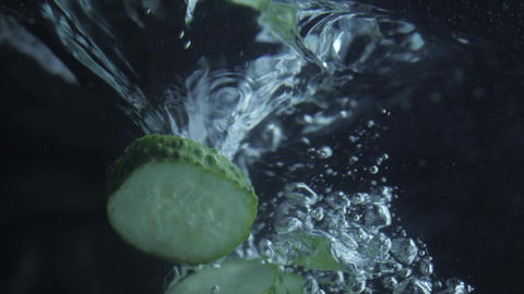 Cucumber slices splashing and falling into water Footage