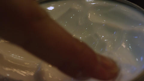 Hands getting moisturizer from container closeup Footage