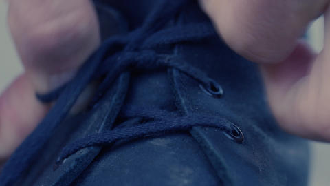 Hands tying shoelaces on boot, closeup Footage