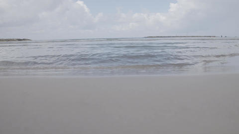 Timelapse of small waves crashing on sand and feet running past Footage
