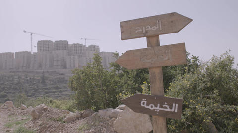 Old wooden signpost with Arabic writing at a crossroad Footage
