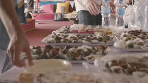 People choose desserts from a catering table Footage
