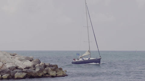 Blue sailboat withstands large waves near rocky shore Footage