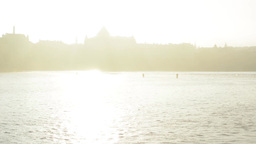 sunrise - river bank (grass) - reflection sun in water - silhouette city Footage