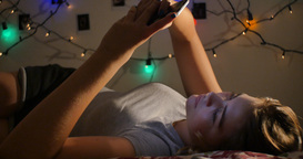 Young teenage girl relaxing on bed with social media on mobile smart phone Footage