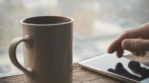 Ceramic cup, mobile phone on a window sill against a window with rain drops Live Action