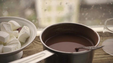 Marshmallow in a cup, cocoa in a saute pan on a window sill against the window Footage