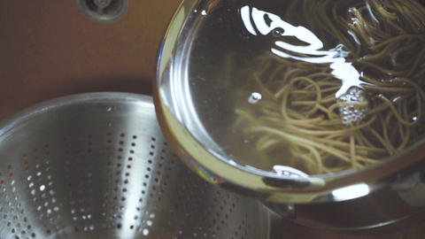 Transfusion of buckwheat noodles with water from a glass bowl into a colander Footage