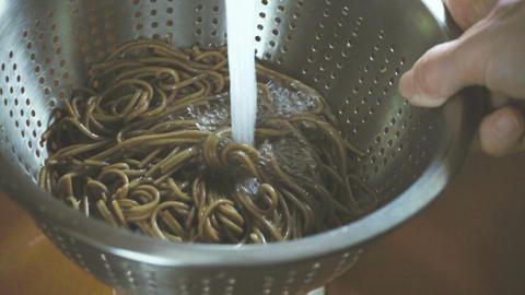Washing buckwheat noodles under running water Footage