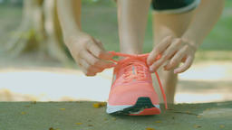 young woman in fitness wear tying shoelaces outdoors Filmmaterial