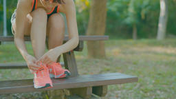 young woman in fitness wear tying shoelaces outdoors Live影片