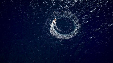 Aerial view of a motor boat designing a circle in the sea navigating fast Footage