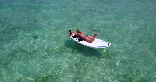 v08070 2 pretty young girls on a surfboard paddleboard with aerial view in warm Fotografía