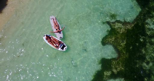 v08333 2 pretty young girls on a surfboard paddleboard with aerial view in warm フォト