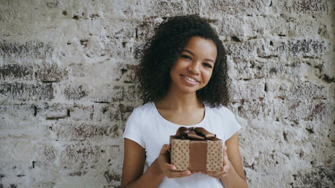 Portrait of young african american woman holding gift box and smiling into Footage