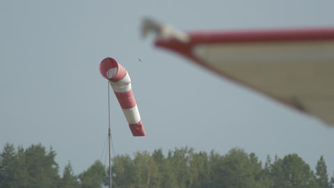 Red-white windsock flutters in the wind on a field near small aircrafts Footage