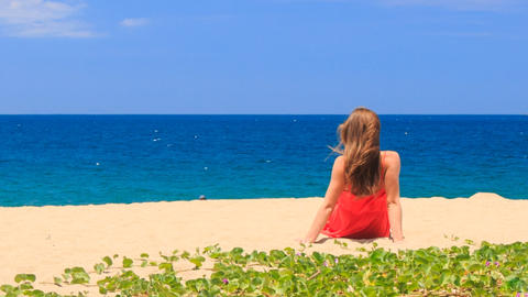 blond girl in red backside sits on beach with hands behind back Footage