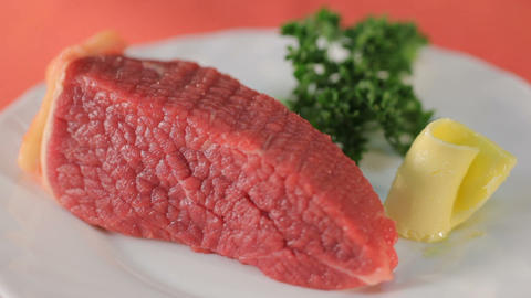 Fillet of raw meat, green and butter on white plate Footage