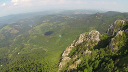 Aerial: Following a distant paraglider over beautiful nature Footage