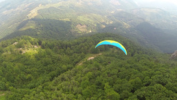 Aerial of paraglider flying over green forest Footage
