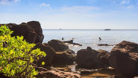 People Swim in Sea near Rock Beach Boats Drift past Footage