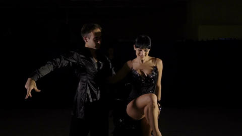 Professional latino dancers in black clothes dancing in the studio Live Action