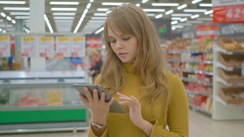 Young woman in the store checking list of products on touch pad Footage