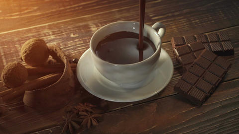 cup of hot chocolate, cinnamon sticks, nuts and chocolate bar on wooden table Footage