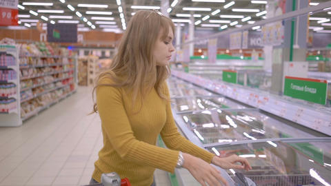 Attractive young woman coming up to the fridge in the shop and taking product Footage