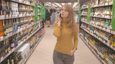 Woman with mobile talking and deciding what wine to buy in supermarket Footage