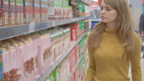 Lovely young girl choosing pack of juice in supermarket Footage