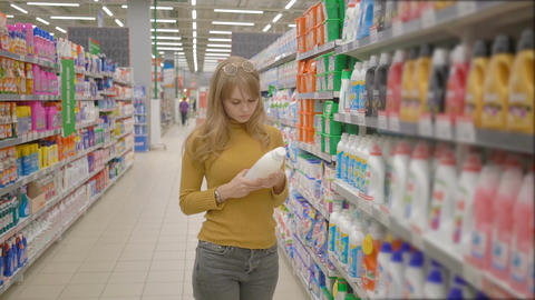 Pensive young woman is choosing household products while doing shopping at the Footage