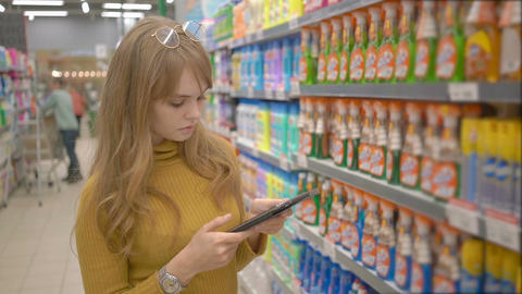 Woman shopping at the supermarket and using mobile apps on her tablet Footage